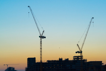 Silhouette of two massive construction cranes with sky at sunset
