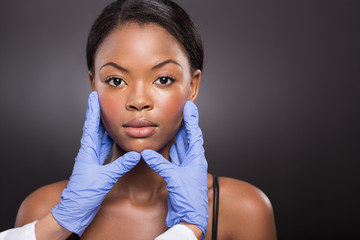 plastic surgeon checking young african woman face