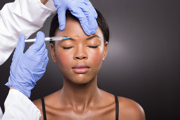 cosmetic doctor injecting african woman forehead