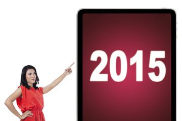 Woman pointing at numbers 2015 on board