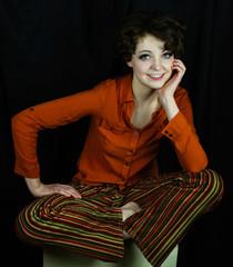 Woman wearing orange shirt and striped pants