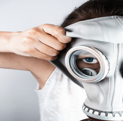 Close-up of woman putting on gas mask