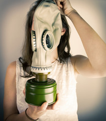 Woman holding gas mask in front of her face