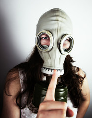 Woman wearing gas mask close-up with one finger held up
