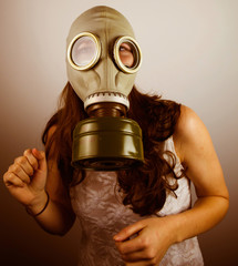 Woman wearing gas mask looking scared