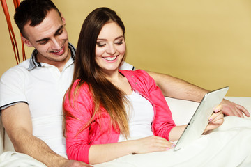 Young couple with tablet sitting on couch at home