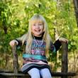 Happy Blond Girl Sitting on Wooden Garden Fence