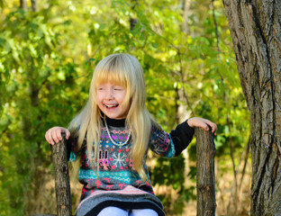 Happy Little Girl Sitting on the Wooden Fence