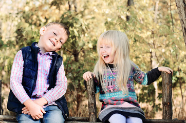 Happy White Kids Sitting on Wooden Garden Fence