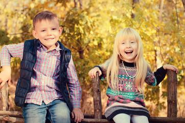 Happy Little Kids Sitting on a Wooden Garden Fence