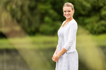 young woman standing by the lake