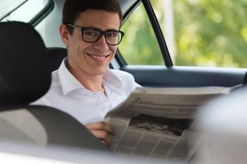 Man reading newspaper in car