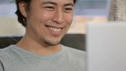 Tilt shot of a young man with a laptop
