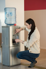Young woman using water dispenser at office