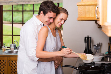 young man hugging girlfriend while she cooks for breakfast
