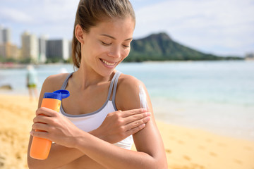 Sunscreen fitness woman applying suntan lotion