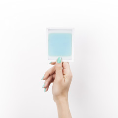 Female hand holding polaroid with blue blank space vertical
