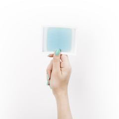 Female hand holding polaroid with blue blank space