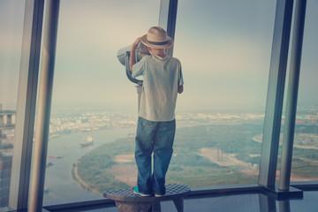 little boy looking through a telescope from a skyscraper