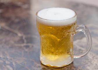 one mug of light beer on the table