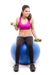 Lifting dumbbells on swiss ball