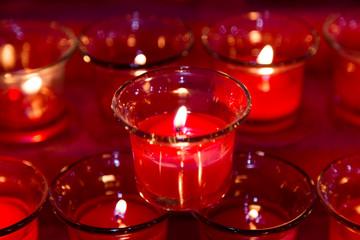 Red tea lights in glass jar illuminates a dark surrounding