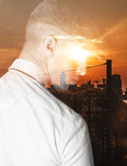 Double exposure of thoughtful man and city sunset