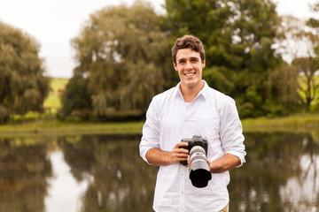 young man holding digital camera