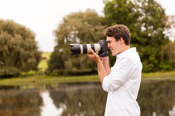 young man taking photos outdoors