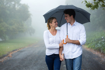 couple walking under umbrella in forest