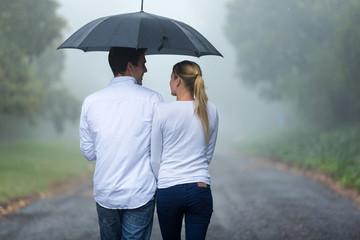 rear view of couple walking in rain