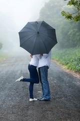 young couple hiding behind the umbrella