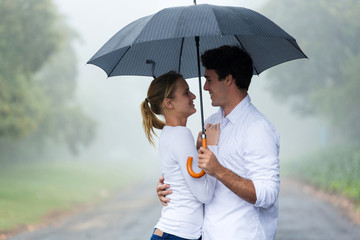 young woman with boyfriend under an umbrella