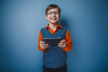 European-looking boy of ten years in glasses plays in tablet, sm
