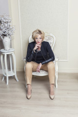 beautiful young blond woman sitting on a chair