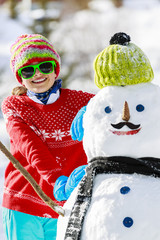 Winter fun, happy girl playing with snowman