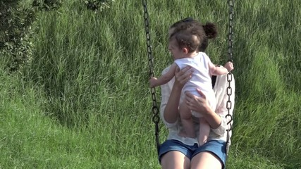 mother and her baby swing together in the playground