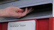 Slow motion of person hand posting a letter in a mail letter box