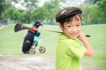 Little boy taking golf club on white background