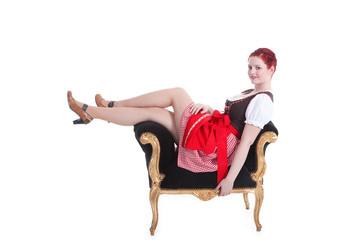 Junge rothaarige Frau im Dirndl sitzt auf Barock Hocker