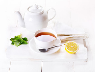 cup of tea and teapot with lemon and mint