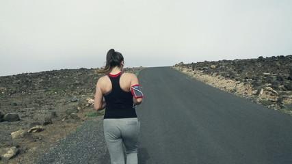 Woman jogging up through road