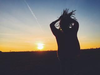 Mädchen springt vor Abendhimmel