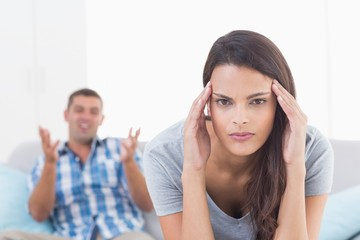 Woman suffering from headache while man arguing