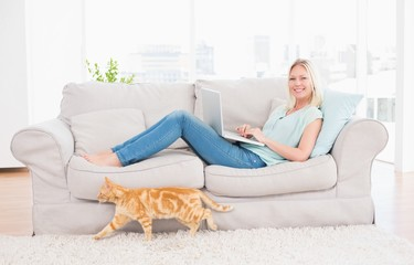 Woman using laptop on sofa while cat passing by