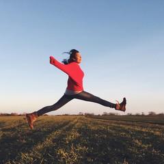 glückliche Frau springt über ein Feld