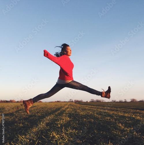 canvas print picture glückliche Frau springt über ein Feld