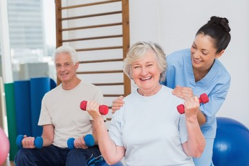 Senior woman lifting dumbbells while sitting with man