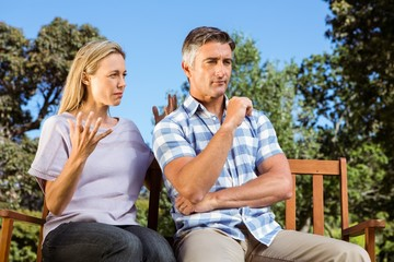 Couple having an argument on park bench