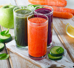 Vegetable juices on a white wooden background